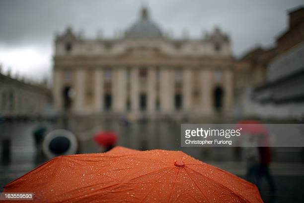 A pilgrim waits in the rain in St Peter's Square as cardinals start their conclave on March 12 2013 in Vatican City Vatican Pope Benedict XVI's...
