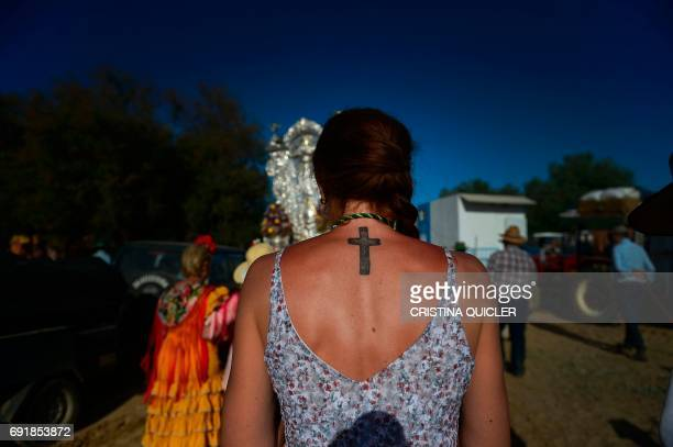 A pilgrim with a cross tattooed on her back walks on the Ajoli in the village of Rocio during the annual El Rocio pilgrimage on June 3 2017 in...