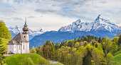 Classic view of Maria Gern pilgrimage church embedded in idyllic scenery with famous Watzmann mountain top in the background on a beautiful sunny day with blue sky in springtime, Bavaria, Germany