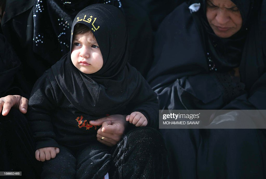 Pilgrims and a child taking part in the Arbaeen religious festival which marks the 40th day after Ashura commemorating the seventh century killing of Prophet Mohammed's grandson, Imam Hussein, in the shrine city of Karbala, southwest of Iraq's capital Baghdad, on January 1, 2013.