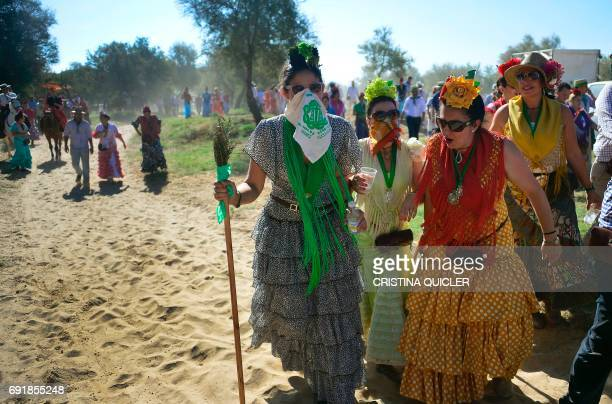 Pilgrims cover their mouths with handkerchiefs as they walk to cross the Ajoli bridge in the village of Rocio during the annual El Rocio pilgrimage...