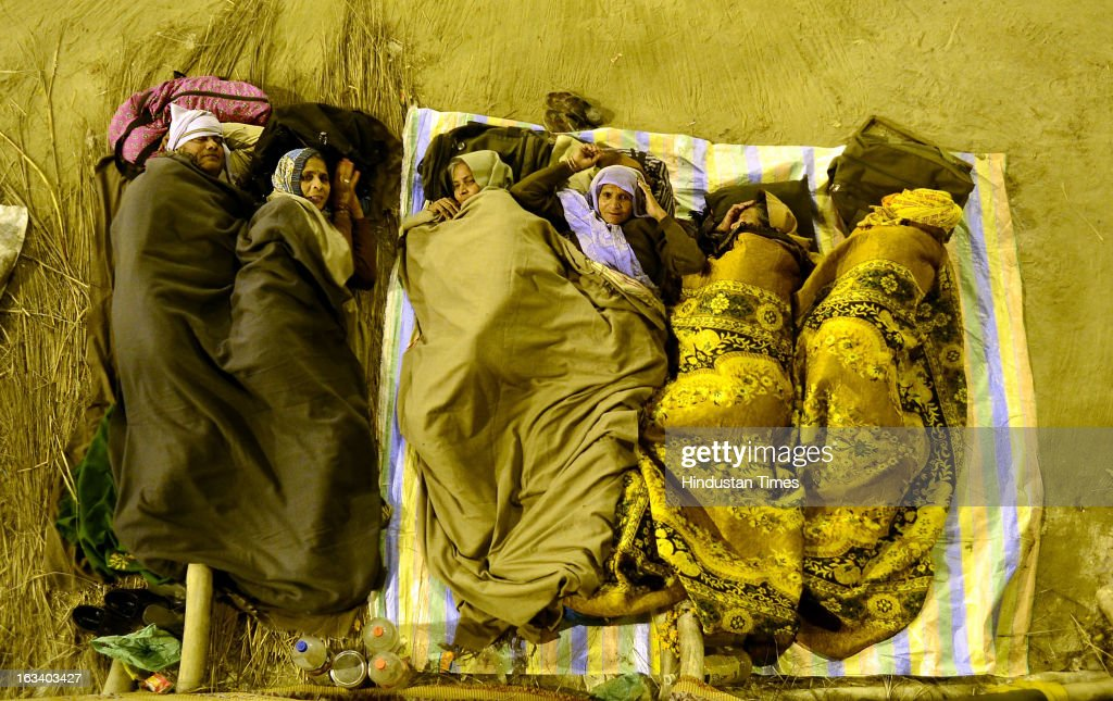 Pilgrims get ready to spend the night under the skies on the banks of Sangam in a Kumbh Mela area on March 9, 2013 in Allahabad, India. The mega religious fair, held once in 12 years, last official bathing on 'Maha Shivratri' on March 10, 2013.