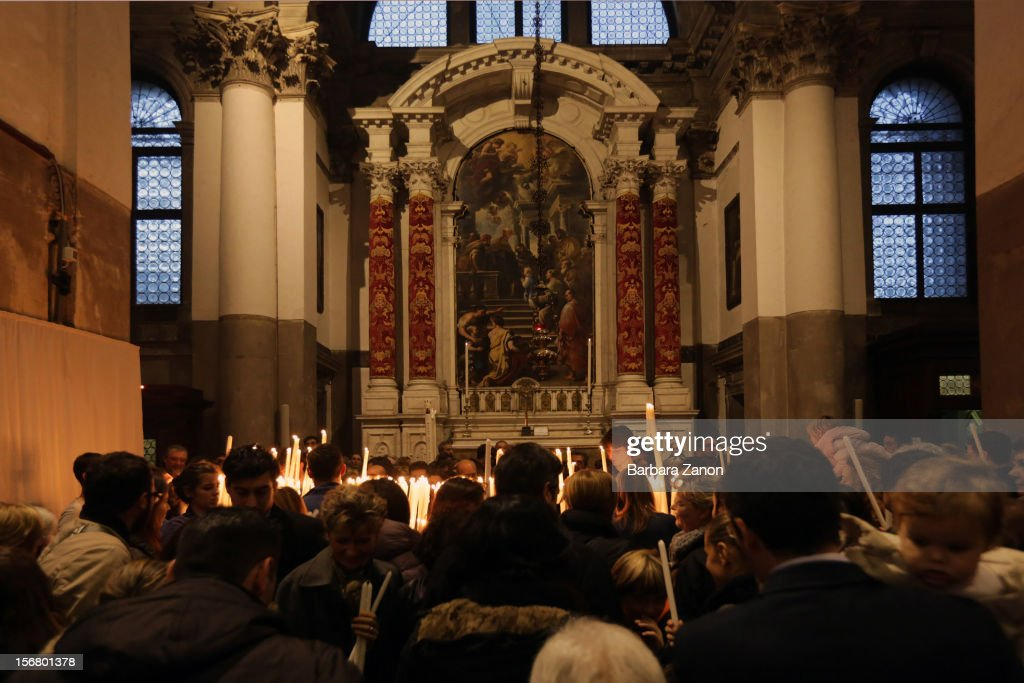 Pilgrims hold candles inside the Church during the Santa Maria Della Salute celebrations on November 21, 2012 in Venice, Italy. During the annual Santa Maria Della Salute celebrations, Venetians make pilgrimage to the Church to give thanks to the Virgin Mary (Maria), who is believed to have brought an end to the plague which struck the city in 1629.