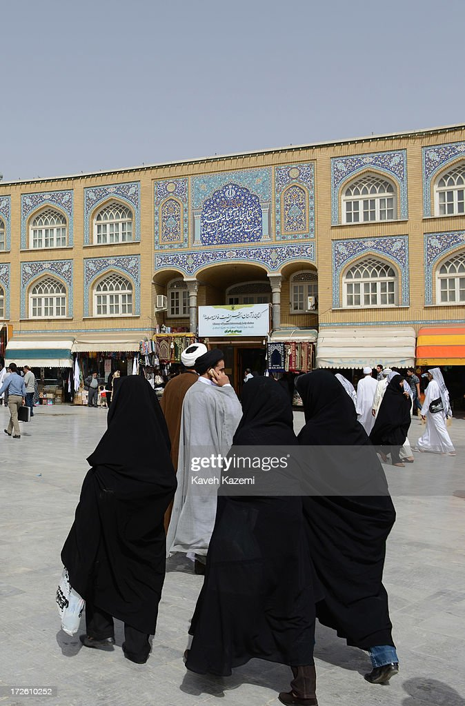 Pilgrims in black chadors walk on the grounds outside the holy shrine of Fatima on June 12 2013 in Qom Iran Qom is the heart of Shiite Islam with...