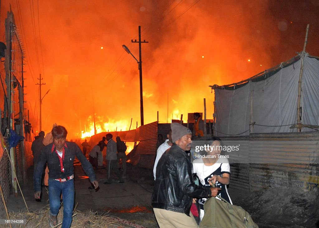 Pilgrims in panic flee their camp as fire engulfs their tent in the Kumbh Mela area on February 15, 2013 in Allahabad, India. A sadhu was reportedly dead in early morning fire at Kumbh Mela Camp.
