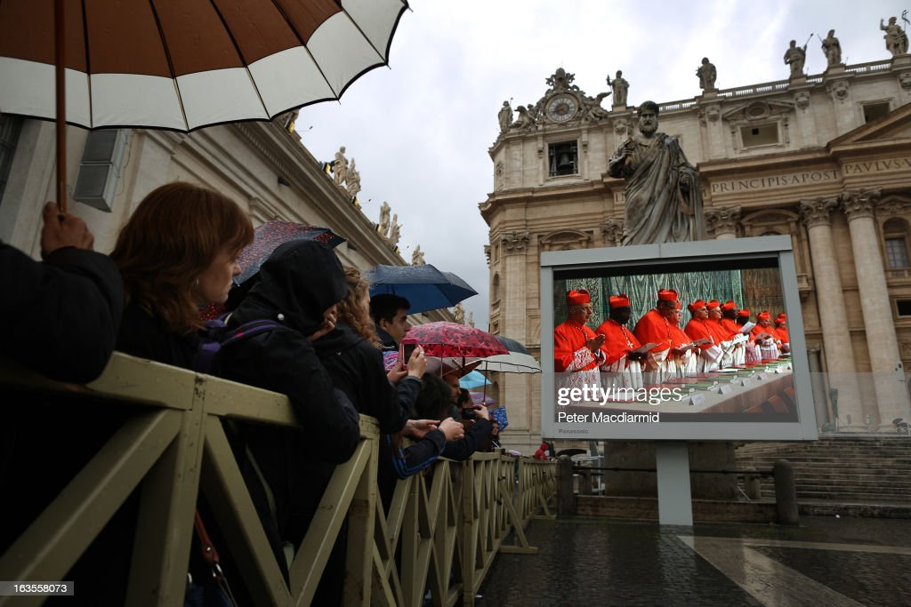 Pilgrims in St Peter's Square watch a giant television screen showing a mass being held in the basilica on March 12, 2013 in Vatican City, Vatican. Pope Benedict XVI's successor is being chosen by the College of Cardinals in Conclave in the Sistine Chapel. The 115 cardinal-electors, meeting in strict secrecy, will need to reach a two-thirds-plus-one vote majority to elect the 266th Pontiff.