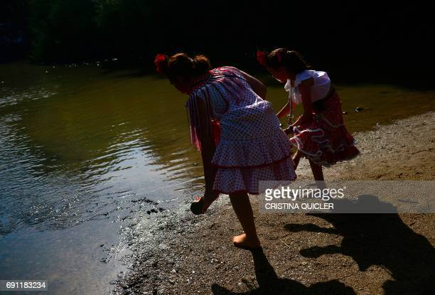 Pilgrims in traditional costume removes their shows before crossing the Quema river during the annual El Rocio pilgrimage in Villamanrique near...