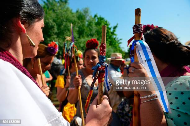 Pilgrims in traditional Rocio costume with a stick with the colors of their brotherhood and a flower in their hair gather near the Quema river during...