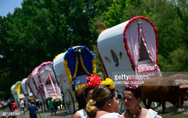 Pilgrims in traditional Rocio costumes gather in front of wagons near the Quema river during the annual El Rocio pilgrimage in Villamanrique near...