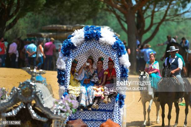 Pilgrims in traditional Rocio costumes sit in a wagon as they cross the Quema river during the annual El Rocio pilgrimage in Villamanrique near...