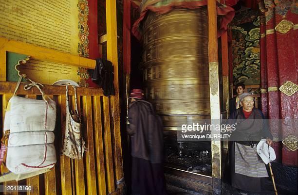 Pilgrims near a huge prayers wheel at jokhang temple barkhor circuit Lhasa Tibet in Lhasa China