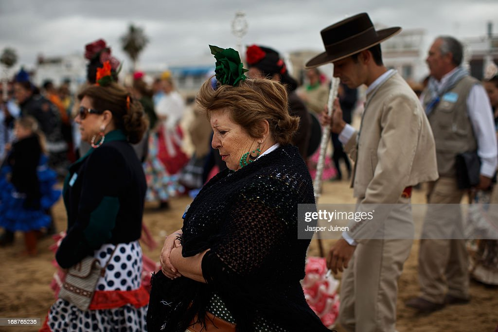 Pilgrims of the Chipiona and the Sanlucar de Barrameda hermandades walk the Playa de Vajo de Guia to board a vessel to cross the Guadalquivir river during their journey to the small town of El Rocio on May 15, 2013 in Sanlucar De Barrameda, Spain. The Romeria del Rocio procession brings together roughly a million pilgrims each year making their way for as long as seven days from throughout Andalusia by foot, on horsebacks and horse drawn carriages, to the doors of the Hermitage of El Rocio. On Sunday night, after reciting the Holy Rosary at candlelight, and the passing of all the simpecados in front of the chapel, with the one from the brotherhood of Matriz de Almonte as the last one, el salto de la reja begins, the jumping of the fence surrounding the Hermitage after which the Virgin of El Rocio is carried out onto the sandy streets of the small town for the 'Blanca Paloma' procession. Then, the long camino home begins. Dating back from 1653, it was in 1758, when the Virgin of Las Rocinas became known as the Virgin of El Rocio, that the pilgrimage started to take place in the weekend of the Sunday of Pentecost, 50 days after Easter Sunday.