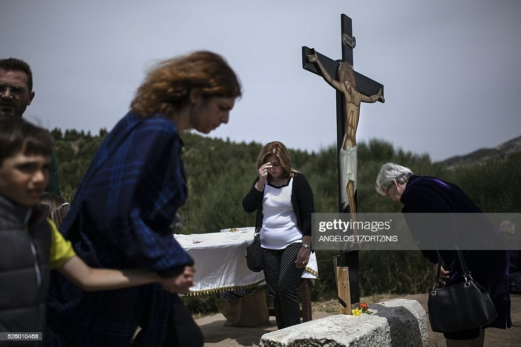 Pilgrims of the Greek Orthodox Church stand in front of an image of Jesus crucified during the ceremony marking the Apokathelosis, the removal of Christ's dead body from the Cross, which forms a key part of Orthodox Easter, in a ceremony at the Church of the Dormition of the Virgin in Penteli, north Athens on April 29, 2016 Millions of Greeks flock to churches around the country this week to celebrate Easter, the country's foremost religious celebration. / AFP / ANGELOS