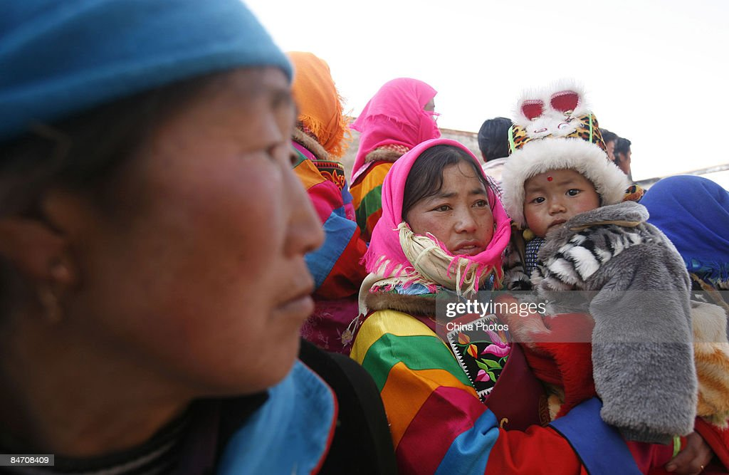 Pilgrims of Tu ethnic minority group attend the 'Tiaoqian' praying ceremony at the Youning Temple on February 8, 2009 in Huzhu County of Qinghai Province, China. The Youning Temple holds the annual 'Tiaoqian' ceremony in the first lunar month each year. During the ceremony, monks will wear colourful traditional clothes and masks, performing the 'Fawang Dance' and 'Horse-headed Warrior Dance' to scare away evil spirits. Pilgrims also pray for good luck during the ceremony.