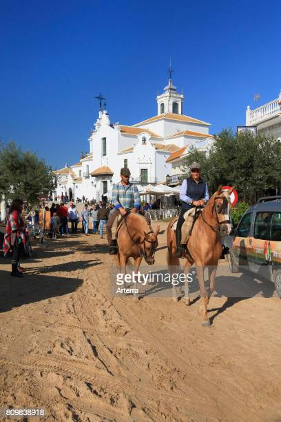 Pilgrims on horseback near the white Hermitage of El RocÕo / Ermita del RocÕo Almonte Province of Huelva Andalucia Spain