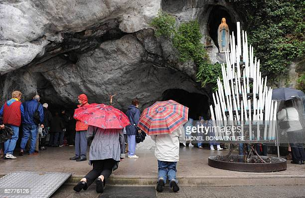 Pilgrims pray at the Grotto of Massbielle at the Sanctuary of Lourdes on September 11 2008 ahead of the visit of Pope Benedict XVI who will...