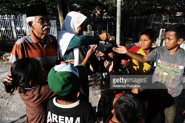Pilgrims visiting the graves of family members before Ramadan give money to children begging at the cemetery on July 9 2013 in Surabaya Indonesia...