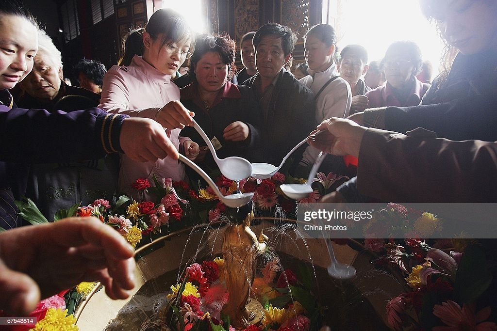 Pilgrims wash the statue of Buddha with fragrant water during the Bathing Buddha Ceremony to mark the Buddha's birthday at Zhengjue Temple one of...