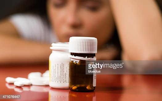 Pill bottles with pills next to them and a woman in back