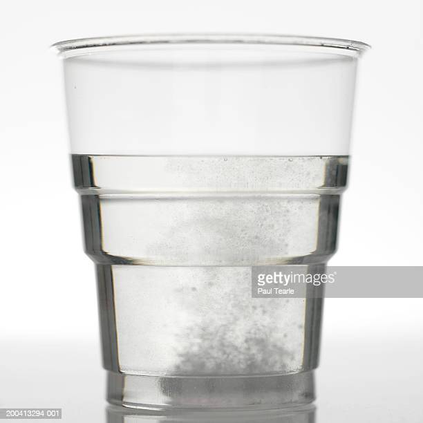 Pill fizzing in glass of water, close up