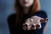 Close up of white pill with smiley face on a hand held by a young, ginger girl