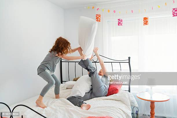Pillow fight between mother and daughter in home bedroom.