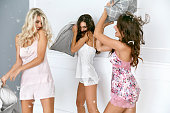 Pillow Fight. Sexy Women Having Fun At Home Party. Beautiful Smiling Female Models In Stylish Sexy Pajamas Playing And Fighting WIth Pillows At Pajama Party. High Resolution