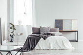 Decorative pillow with houndstooth pattern placed on the bed in white room with window and simple lamp
