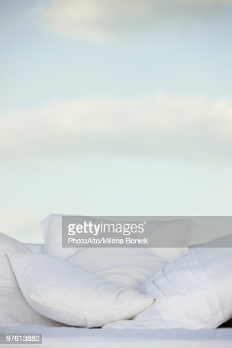 Pillows against background of clouds in pale sky