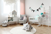 Children room interior decorated with stuffed animal toys, and colorful pillows that come in various shapes