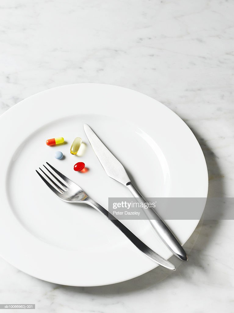 Pills and capsules on plate, elevated view, close-up : Stock Photo