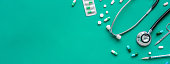 Pills and medical equiupments including stethoscope, syringe and scissors at border on green banner background, top view with copy space