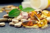 pills and multivitamins on a dark background, closeup