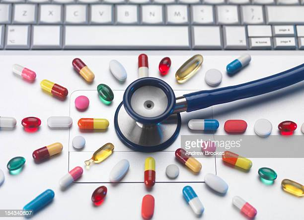 Pills and stethoscope on laptop