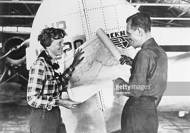 Pilot Amelia Earhart and her navigator Fred Noonan with a map of the Pacific that shows the planned route of their last flight