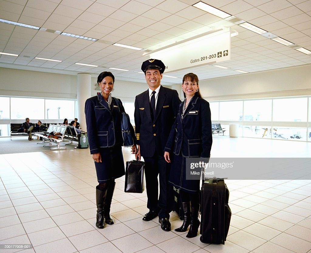 Pilot and flight attendants in airport lounge, portrait : Stock Photo