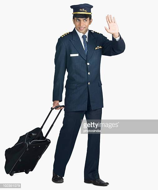 Pilot carrying his luggage and waving his hand
