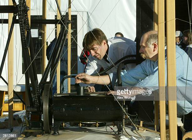 Pilot Chris Johnson and engine specialist Greg Cone test run the engine of a reproduction of the 1903 Wright Flyer December 15 2003 at the Wright...