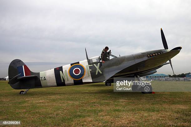 A pilot climbs into a Spitfire on August 18 2015 in Biggin Hill England Aircraft including 18 Spitfires and six Hurricanes flew over southern England...
