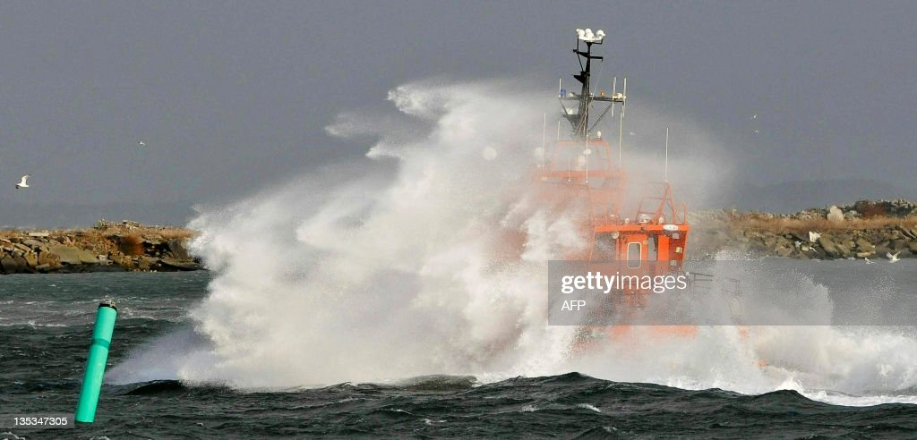 A pilot cutter is submerged by spray as it passes outside Malmo harbour breakwater on December 9, 2011. The first winter storm has created havoc in Sweden, with trucks careening off icy roads in the South and up to 25 centimetres (10 ins) of snow and harsh winds in the North. More than 12.000 homes were without power on December 9. AFP PHOTO/SCANPIX-SWEDEN/SCANPIX-SWEDEN