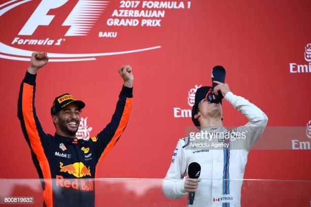 Pilot Daniel Ricciardo of Australia and Red Bull Racing celebrates his victory as 3rd ranked Williams Martini Racing's Lance Stroll stand next to him...