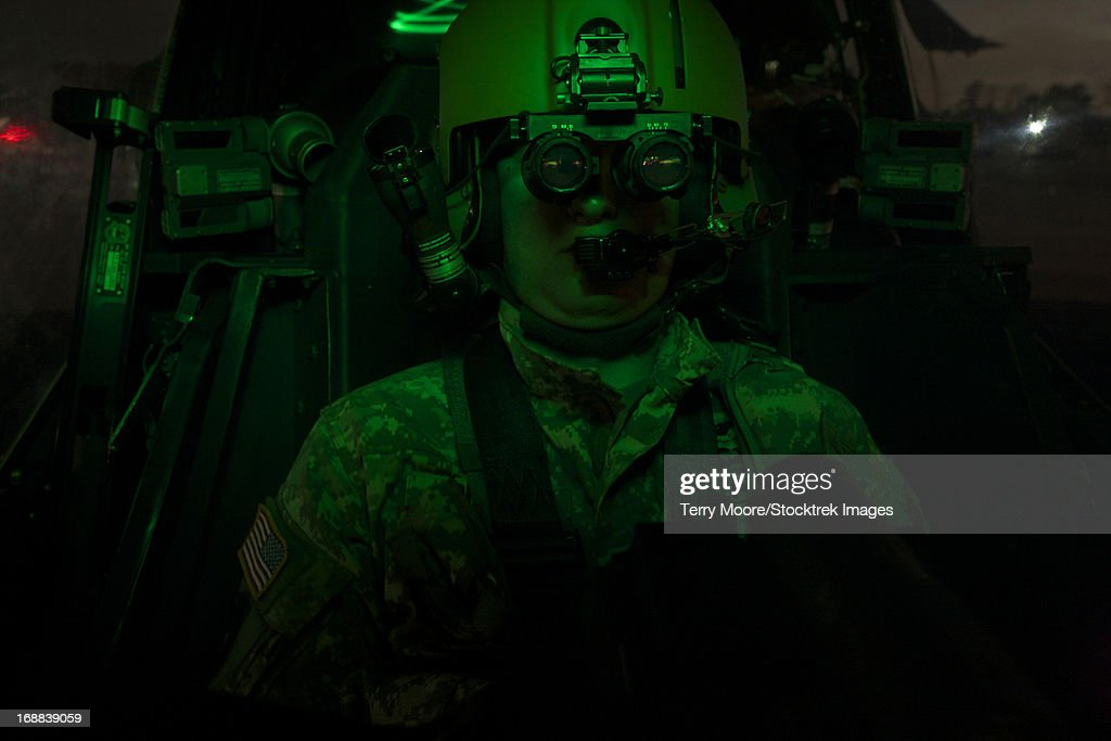 A pilot equipped with night vision goggles in the cockpit of an AH-64 Apache helicopter.