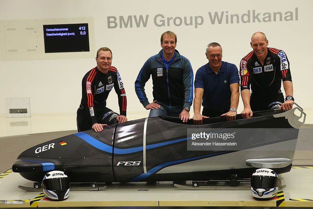 Pilot Francesco Friedrich (L) and Alexander Mann (R) of Team Germany 1 pose with Christof Langen (2nd L), head coach of Bobsleigh Germany and aerodynamicist Norbert Gruen at their new Bobsleigh FES 208 in the Wind tunnel of Technology Partner BMW on October 29, 2013 in Munich, Germany.