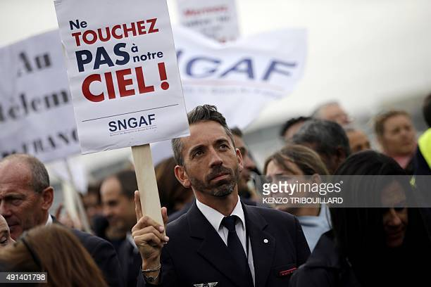 A pilot holds a placard reading 'do not touch our sky' during a demonstration next to the Air France headquarters in RoissyenFrance on October 5...
