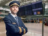 Porträt eines Piloten in der Uniform mit goldenen Streifen und Mütze kreuzte seine Arme. Er steht im Terminal eines Flughafens