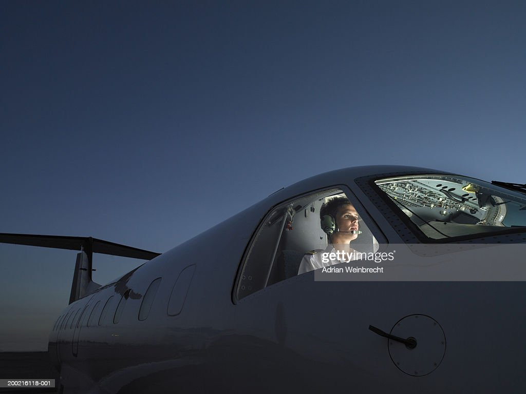 Pilot in illuminated cockpit of plane wearing headphone, looking ahead