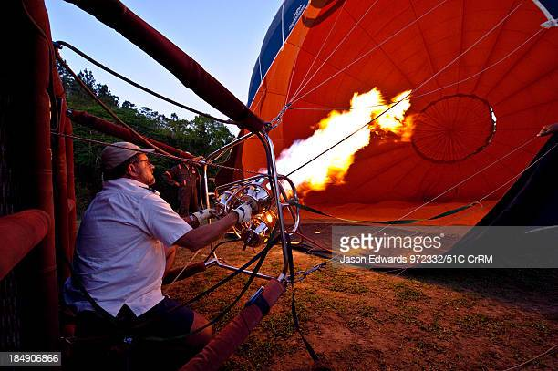 A pilot inflates a balloon canopy with hot air preparing for liftoff Viti Levu Pacific Ocean Fiji Islands
