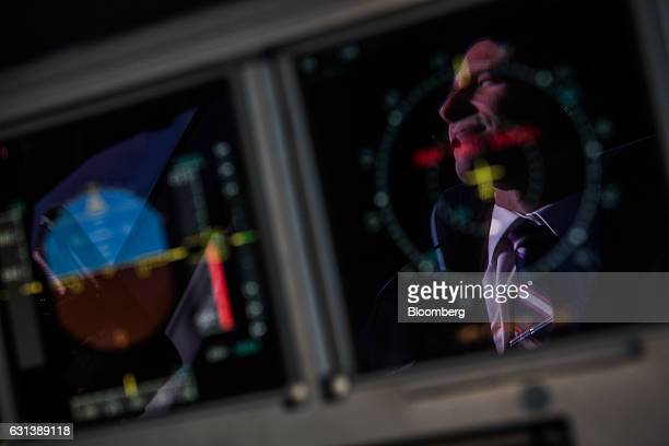 A pilot is reflected in a flight control screen inside the cockpit onboard a passenger aircraft operated by Wizz Air Holdings Plc at Liszt Ferenc...