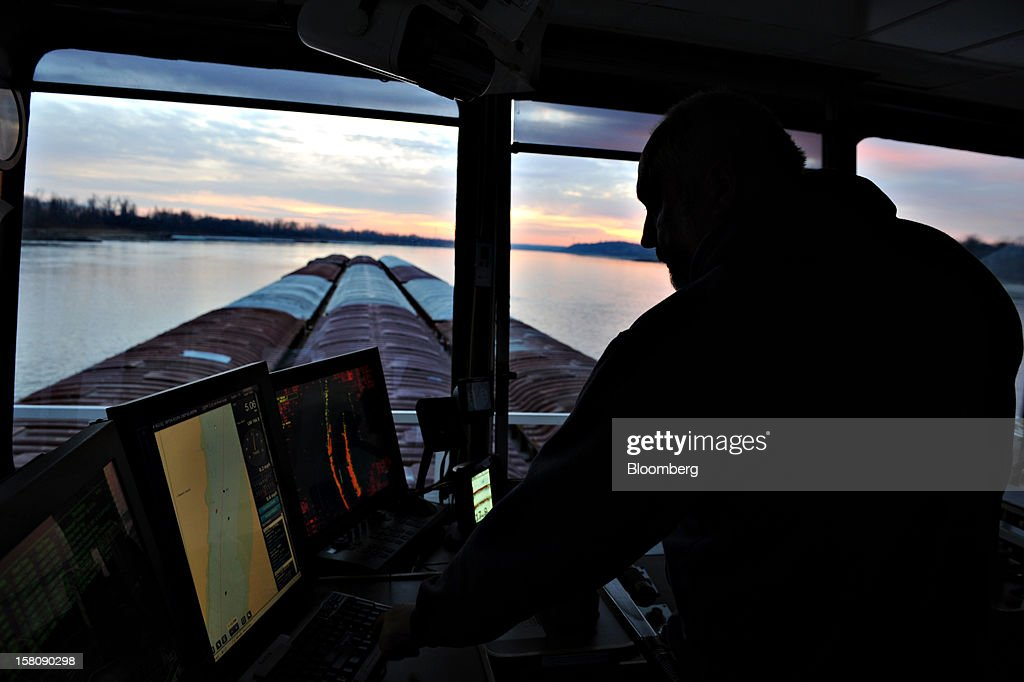 Pilot Jeff Heflin, aboard the Capt. Bill Stewart tow boat, looks over navigation screens as he directs 15 grain barges on the Mississippi River outside St. Louis, Missouri, U.S., on Thursday, Dec. 6, 2012. Barges carrying grain, soybeans, coal, oil and other commodities on the Mississippi River have started to reduce their loads to navigate waters shrunk by the worst drought in 50 years. Photographer: Daniel Acker/Bloomberg via Getty Images