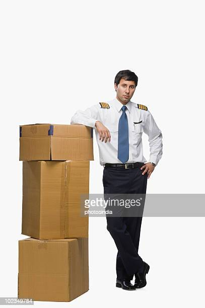 Pilot leaning against cardboard boxes
